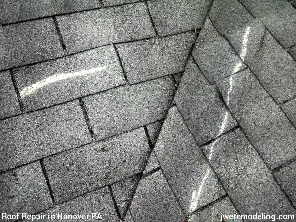 Severe wind damage to asphalt shingles at this Hanover PA roof repair job by JWE roofing contractors