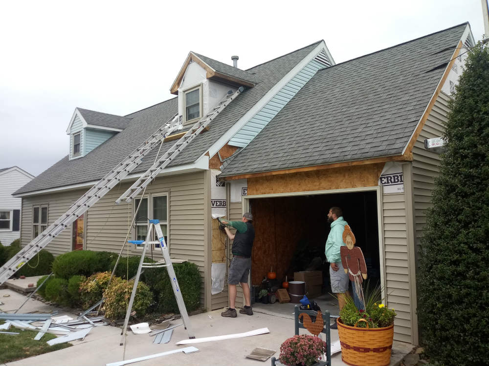 Our siding contractors work on the vinyl clapboard and new fascia, soffit and gutters installation in the front of the house.